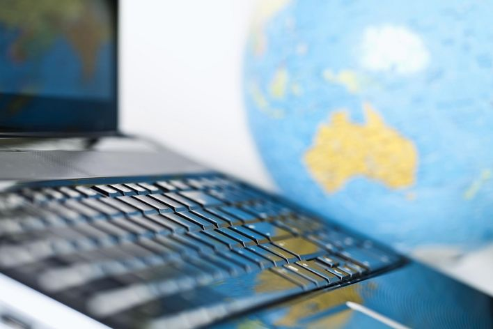laptop on a desk with a globe