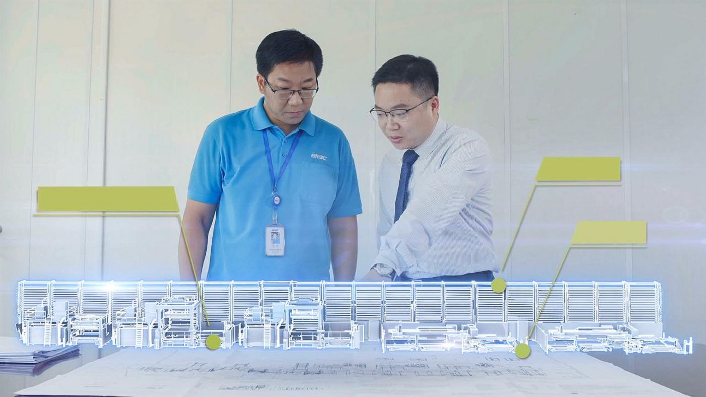 Colleagues in front of a miniature model of production