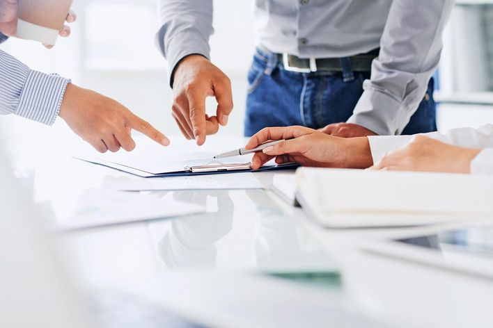 People pointing at documents on a table