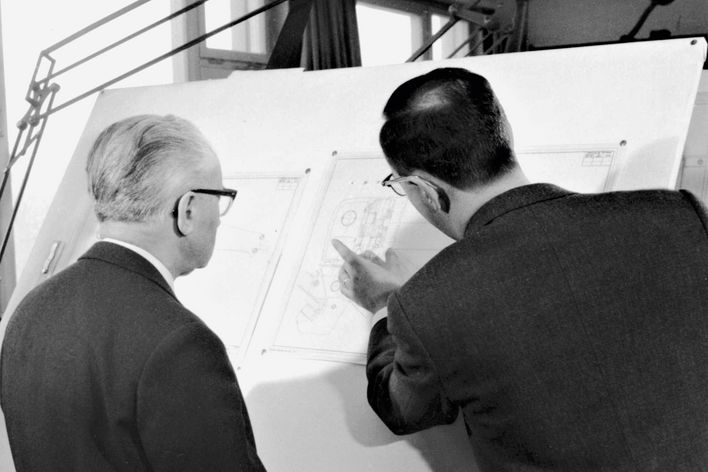 historical picture showing Berthold Leibinger explaning an engineering drawing