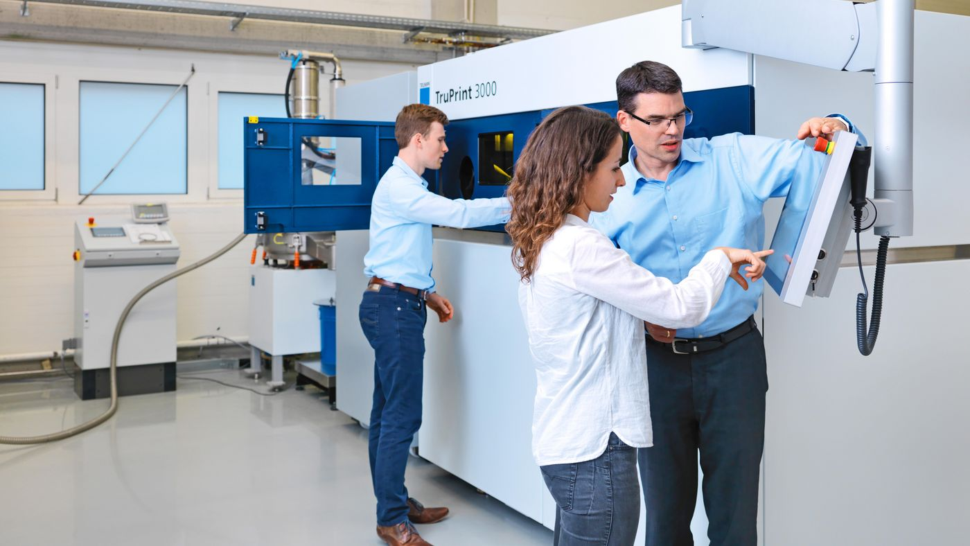 TRUMPF employees talking in front of a TruPrint machine
